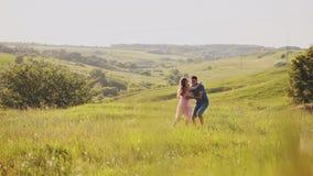 Danza y abrazo atractivos jovenes de los pares en un campo amarillo abierto de par en par en un primer del día soleado metrajes