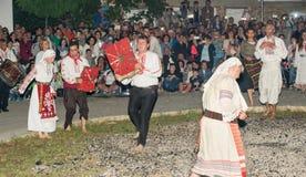 Danzas con los iconos en los carbones calientes en el pueblo de Bulgari, Bulgaria meridional Fotos de archivo libres de regalías