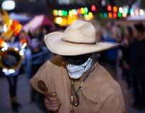 Danzas del hombre y maracas enmascarados de los juegos con un fondo coloreado fotografía de archivo libre de regalías