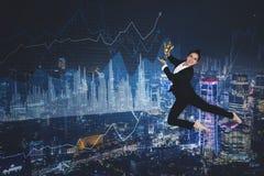 Danzas felices de la empresaria con el trofeo en el cielo imagen de archivo