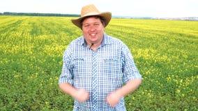 Danzas masculinas gordas felices del granjero divertidas entre los pequeños brotes verdes en el campo el día soleado almacen de metraje de vídeo