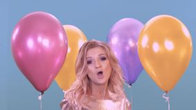 Danzas rubias jovenes de una muchacha en su cumpleaños en un vestido brillante hermoso entre los globos almacen de video