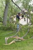 Daño de la tormenta del viento del tornado, árbol tragado motosierra del hombre Foto de archivo