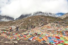 People hiking and welcomed by thousands of colorful prayer flags Royalty Free Stock Photography