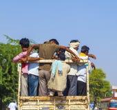 Indiskt folk som står på lastområdet av en åka lastbil Arkivbilder
