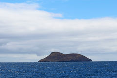 Daphne Major island in the Galapagos chain. View of Daphne Major island in the Galapagos National Park, Ecuador, from the water against a bright blue sky and royalty free stock photos