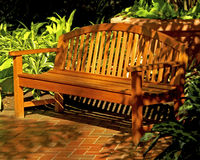Dappled Bench. Horizontal image of a wooden bench with mixed sunlit and shaded areas Stock Photography