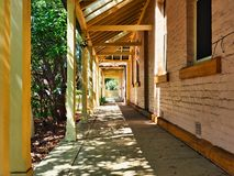 Dappled Shadows on Long Covered Verandah, Australia. Dappled light and shade from trees growing in front of a long covered verandah of an historic heritage brick stock images