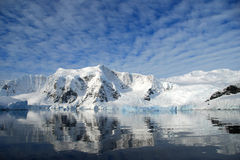 Dappled skies over antarctic mountain landscape. Crisp reflections in sea of antarctic landscape Royalty Free Stock Photography