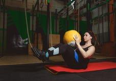 Dar certo a mulher que da aptidão fazer se senta levanta exercícios com bola de medicina Imagens de Stock Royalty Free