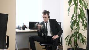 Dar certo no escritório, o homem em um terno faz um exercício para o bíceps ao sentar-se no escritório e ao falar no video estoque