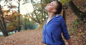 Dar certo no parque A jovem mulher no casaco azul prepara-se correndo esticando seus braços e pés em bonito video estoque