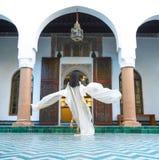 Красивая морокканская девушка развевая ее белая хламида в богатом интерьере живописного Dar Si сказала Riyad в Marrakech стоковая фотография