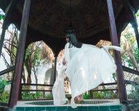 Красивая морокканская девушка развевая ее белая хламида в богатом интерьере живописного Dar Si сказала Riyad в Marrakech стоковое изображение rf