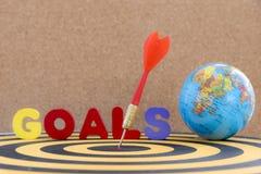 Dardeggi l'obiettivo in centro con gli scopi ed il globo di parola Fotografie Stock