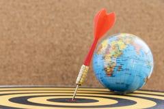 Dardeggi l'obiettivo in centro sul bersaglio con il globo Immagine Stock