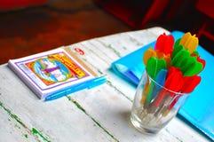 Dardi in un vetro su una tavola nei colori vivi Immagini Stock