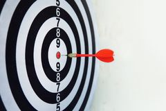 Dardo vermelho a bordo do objetivo do alvo da batida da direção certa Jogo da competição para ganhar o foco na realização com pla foto de stock