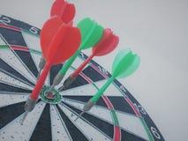 Dardos a bordo de e bullseye no primeiro plano fotos de stock royalty free