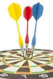 Dardos coloridos que batem um alvo. Fotos de Stock Royalty Free