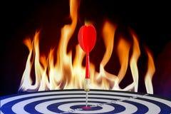 Dards brodés sur la cible avec des flammes du feu photo stock