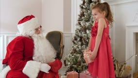 Dare di Santa Claus presente ad una bambina sorpresa stock footage