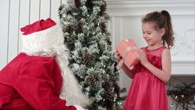Dare di Santa Claus presente ad una bambina sorpresa ed abbracciarla stock footage