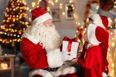 Dare di Santa Claus presente ai bambini nella sala immagini stock libere da diritti