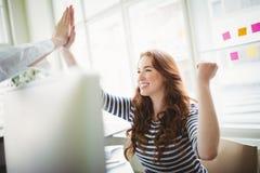 Dare emozionante dei colleghe alto--cinque all'ufficio creativo fotografia stock