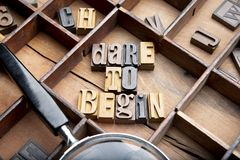 Dare to begin. In wooden typeset letters on rustic background royalty free stock photo