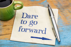Dare to go forward. Handwriting on a napkin with a cup of espresso coffee stock images