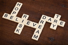 Dare to try - motivational crossword. Motivational concept - hope, believe, risk, dare, try, dream crossword with ivory letter blocks on grunge weathered wood stock photography