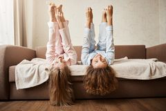 Dare you to touch feet while lying. Portrait of adorable women fooling around and being childish at home in nightwear. Lie on sofa, lifting feet and touching Royalty Free Stock Images