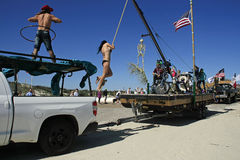 Daredevil Stunts, skeletons, and Flags;  All Part of the Barefoot Mardi Gras Parade. A daring young woman swings from a crane as her float moves through the Stock Photography