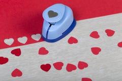 Dargestellter Plastikpapierdurchschlag und handgemachte rote Herzen stockbild