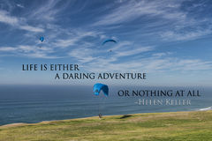 A daring adventure or nothing at all. Paraglider over Torrey Pines in California with the following challenging quote: Life is either a daring adventure or Royalty Free Stock Images