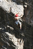 Daring Climb. A rock climber works his way up a rock face protected by a rope clipped into bolts. He is wearing a helmet and quickdraws dangle from his harness Stock Image