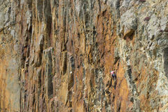 Daring rock climber  on cliff face Royalty Free Stock Image