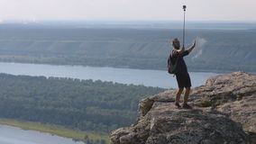 Daring traveler shoots himself with a camera on top of a mountain. stock footage