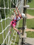 Daring Young Girl on Obstacle Course. Daring young girl climbing on an elevated rope net on an obstacle course.  Reaching for a handhold, expressing courage and Royalty Free Stock Photos