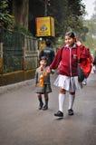 DARJEELING ИНДИЯ - АПРЕЛЬ 2012: Более старая сестра держа сестру руки более молодую на пути к школе в Darjeeling, Индии 12-ого ап Стоковая Фотография