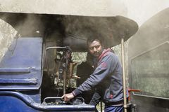 Darjeeling, India, March 3 2017: The locomotive driver drives the steam engine Royalty Free Stock Images
