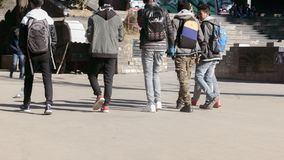 Darjeeling, India - May 2018: Group of smiling friends walking on road at day time. Back view. Cropped image. People having fun stock image