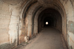 Dark abandoned tunnel interior. With glowing end. Petrovac town, Montenegro Stock Images
