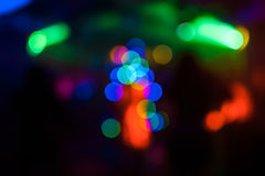 Dark abstract background in night club with colorful bokeh in shape of Christmas tree Royalty Free Stock Photos