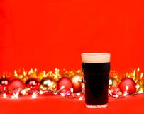Dark ale beer in pint glass with christmas baubles tinsel and li. Nonik pint glass of dark beer or stout ale with christmas lights baubles and tinsel on red royalty free stock image