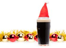 Dark ale beer in pint glass with christmas red hat and christmas. Full pint glass of dark beer or stout ale with Santa Claus or christmas red hat and christmas stock photos