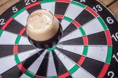 Dark ale and darts Stock Photos