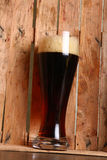 Dark ale in wooden crate Stock Photography