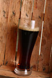 Dark ale in wooden crate Stock Image